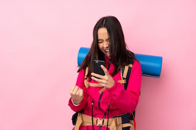 Donna giovane alpinista con un grande zaino con telefono in posizione di vittoria