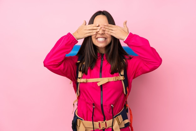 Donna giovane alpinista con un grande zaino sopra isolato muro rosa che copre gli occhi a mano