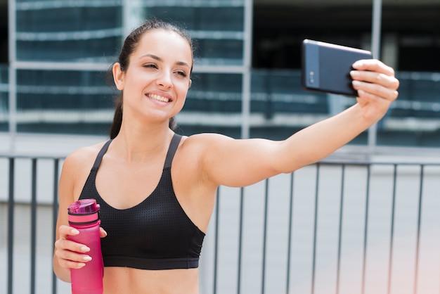 Donna giovane atleta con uno smartphone