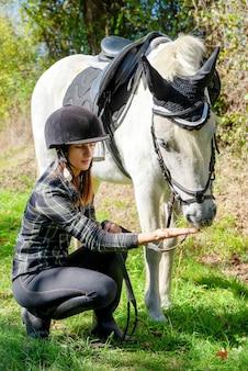 Donna giovane cavaliere con cavallo bianco