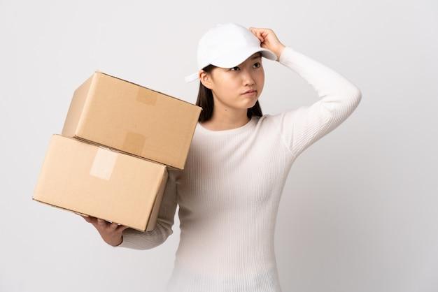 Donna giovane consegna cinese sul muro bianco isolato con dubbi e con espressione del viso confuso