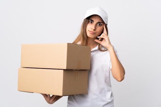 Donna giovane consegna sul muro bianco pensando un'idea