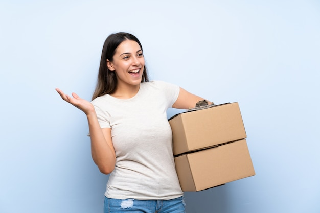 Donna giovane consegna sul muro di mattoni blu con espressione facciale sorpresa