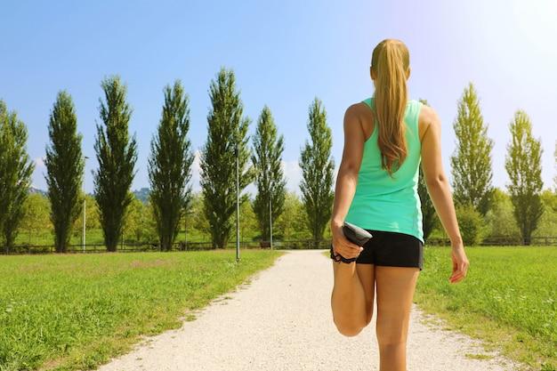 Donna giovane corridore facendo stretching nel parco prima di correre. copia spazio.