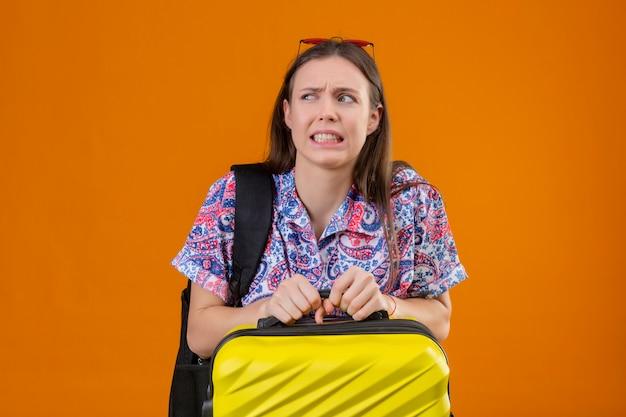 Donna giovane e dispiaciuta e spaventosa del viaggiatore che indossa gli occhiali da sole rossi sulla testa con la valigia della tenuta dello zaino sopra la parete arancio