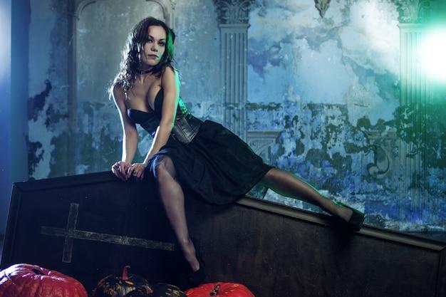 Donna giovane e sexy, immagine delle streghe in un cimitero seduto sulla bara del coperchio.