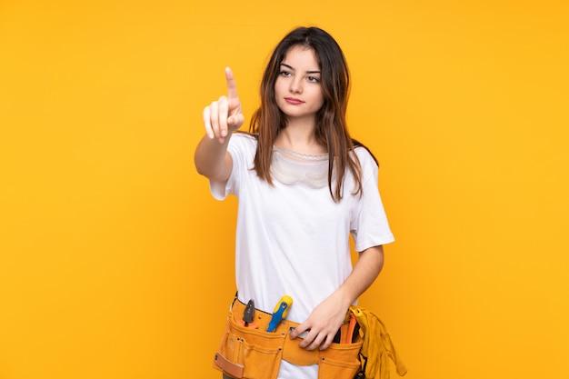 Donna giovane elettricista sopra isolato su giallo toccando sullo schermo trasparente