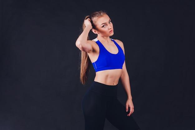 Donna giovane fitness con mani guantate con muscoli addominali stretti