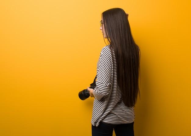 Donna giovane fotografo da dietro pensando a qualcosa
