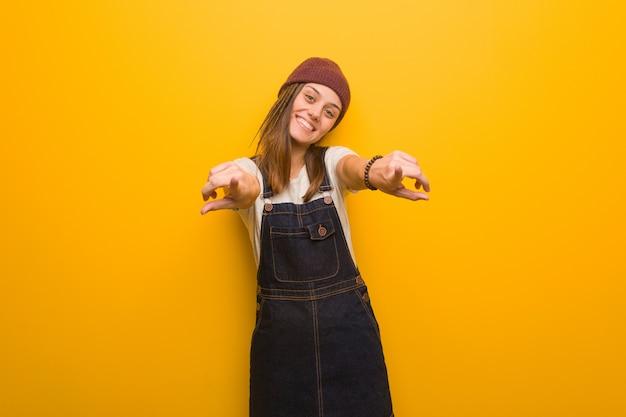 Donna giovane hipster allegra e sorridente che punta alla parte anteriore