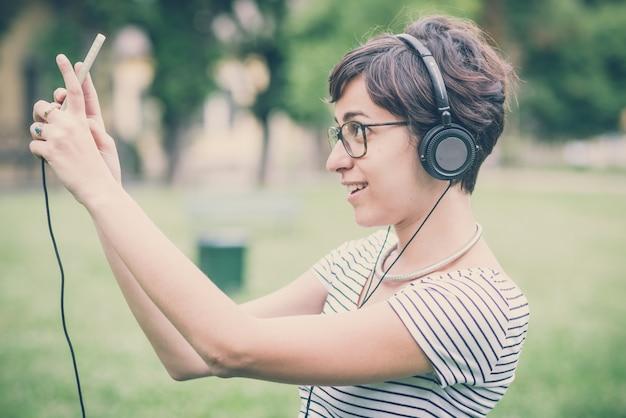 Donna giovane hipster ascoltando musica selfie