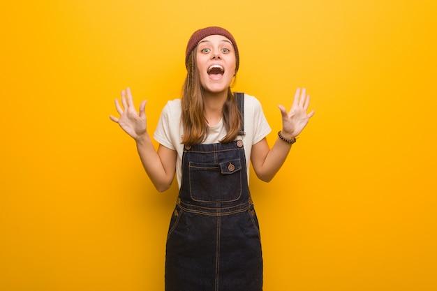 Donna giovane hipster che celebra una vittoria o successo