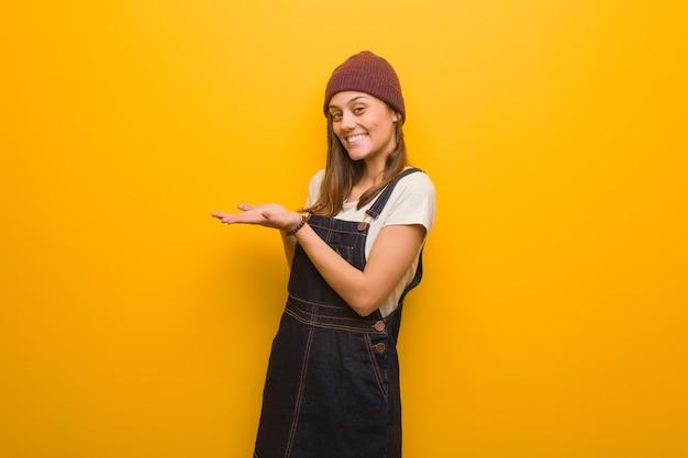 Donna giovane hipster che tiene qualcosa con le mani