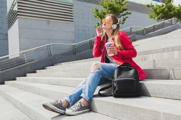 Donna giovane hipster in cappotto rosa, jeans in strada con zaino e caffè ascoltando musica in cuffia, indossando occhiali da sole