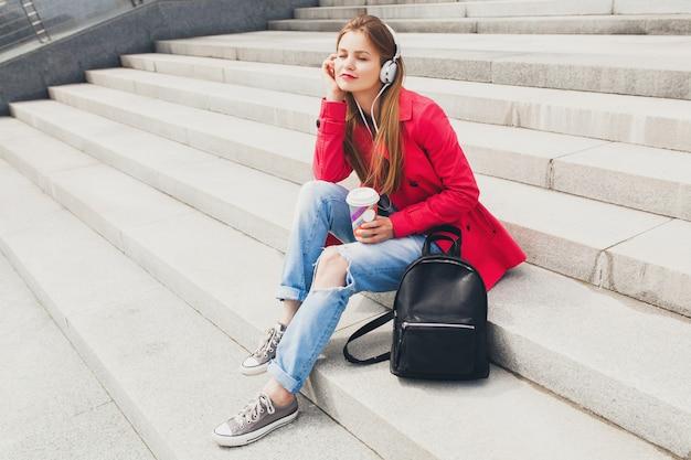 Donna giovane hipster in cappotto rosa, jeans seduti in strada con zaino e caffè ascoltando musica in cuffia, tendenza di stile primaverile urbano della grande città