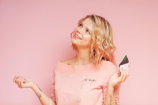 Donna giovane hipster studente con peli colorati e tatuaggio tenendo le carte di credito