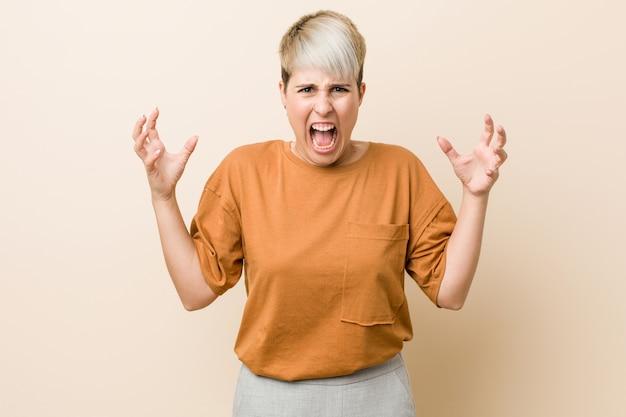 Donna giovane plus size con i capelli corti che grida di rabbia.