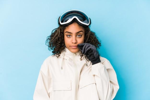 Donna giovane sciatore afroamericano isolata con le dita sulle labbra mantenendo un segreto.