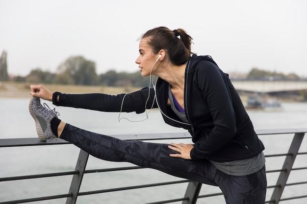 Donna giovane sportivo che allunga le gambe
