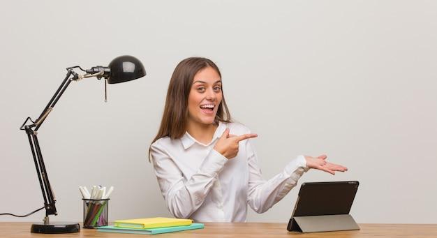 Donna giovane studente che lavora alla sua scrivania tenendo qualcosa con la mano