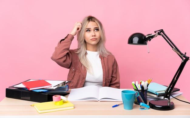 Donna giovane studente che lavora in una tabella con dubbi e con espressione del viso confuso