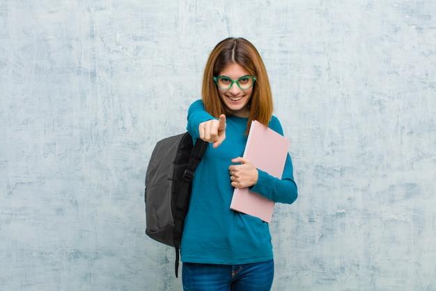 Donna giovane studente che punta alla fotocamera con un sorriso soddisfatto, fiducioso, amichevole, scegliendo il muro del grunge