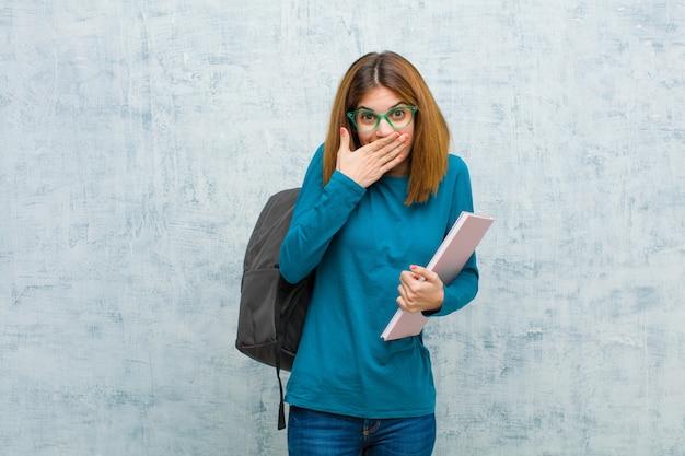 Donna giovane studente che ride di te, indicando la fotocamera e prendendo in giro o deridendoti sulla parete del grunge