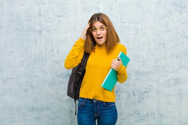 Donna giovane studente che sembra felice, stupita e sorpresa, sorridente e realizzando sorprendenti e incredibili buone notizie su sfondo muro grunge
