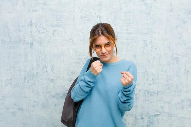 Donna giovane studente che sembra sicura, arrabbiata, forte e aggressiva, con i pugni pronti a combattere nella posizione di boxe contro la parete del grunge