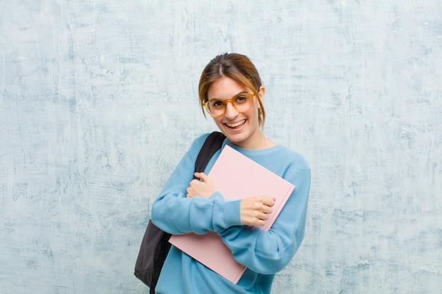 Donna giovane studente che sorride allegramente e festeggia, con i pugni serrati e le braccia incrociate, sentendosi felice e sfondo positivo