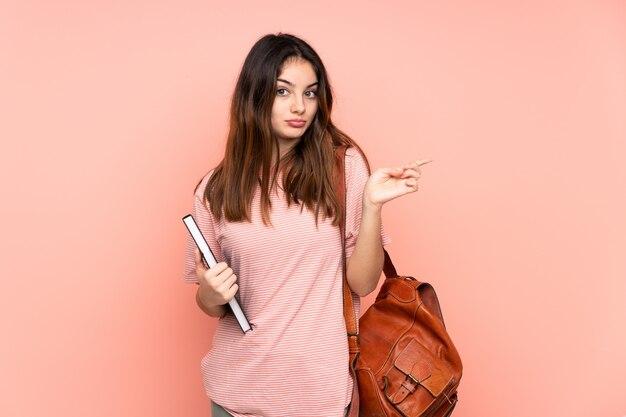 Donna giovane studente che va all'università sul muro rosa indicando i laterali che hanno dubbi