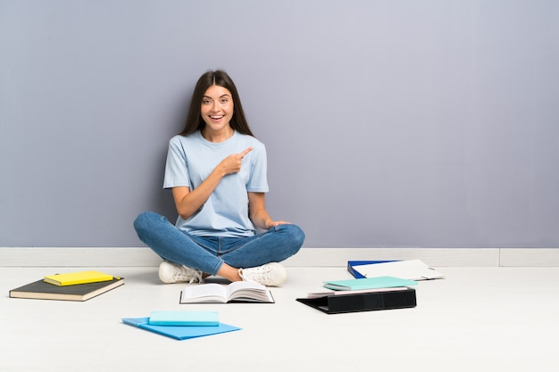 Donna giovane studente con molti libri sul pavimento che punta il dito verso il lato