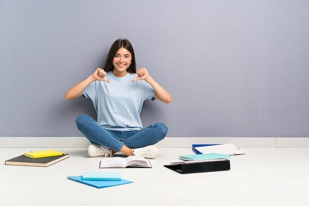 Donna giovane studente con molti libri sul pavimento orgoglioso e soddisfatto di sé