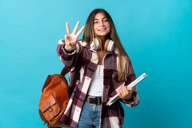 Donna giovane studente isolata su blu felice e contando tre con le dita