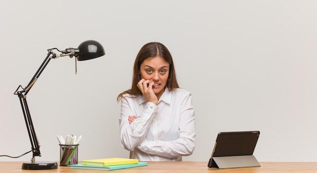 Donna giovane studente lavorando sulla sua scrivania mordere le unghie, nervoso e molto ansioso