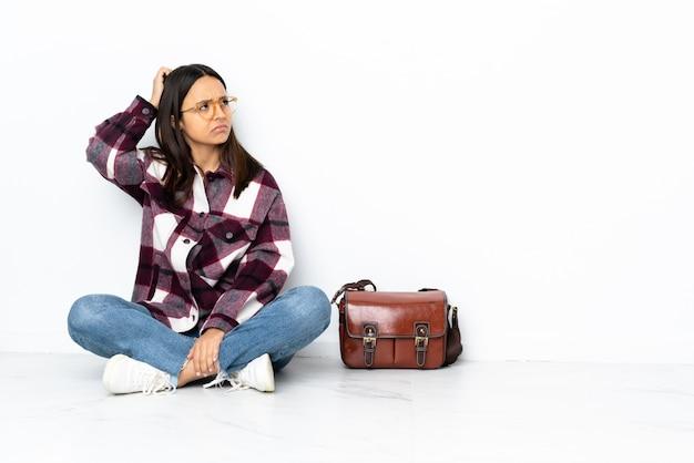 Donna giovane studente seduto sul pavimento con dubbi mentre grattando la testa
