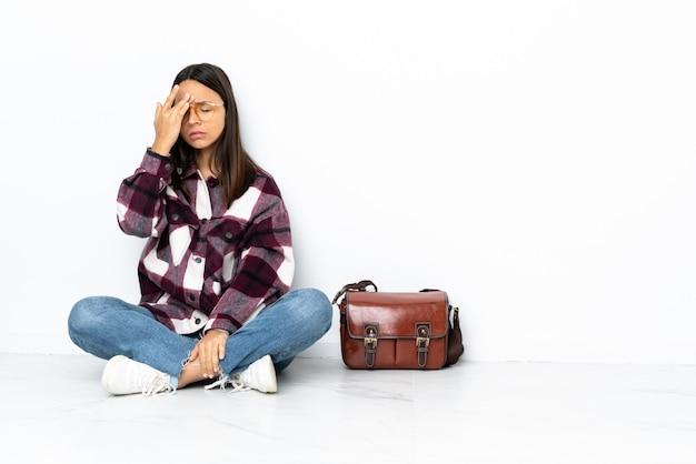 Donna giovane studente seduto sul pavimento con mal di testa