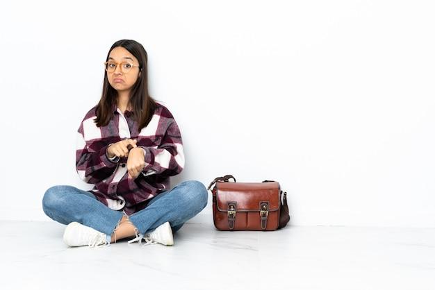 Donna giovane studente seduto sul pavimento facendo il gesto di essere in ritardo