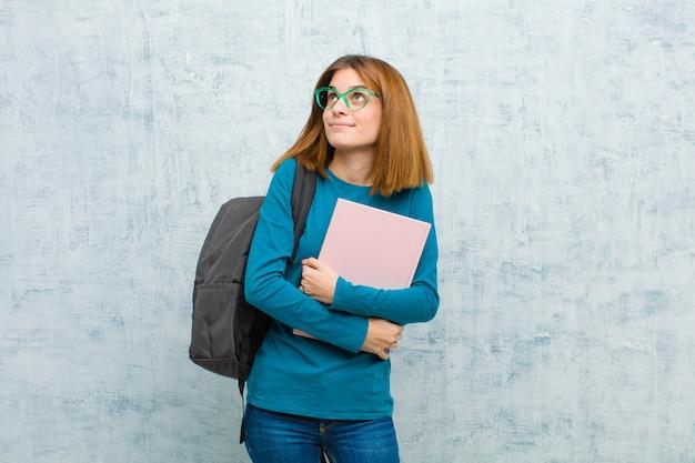 Donna giovane studente sentirsi felice, orgoglioso e fiducioso, chiedendosi o pensando, alzando lo sguardo per copiare lo spazio con sfondo di braccia incrociate