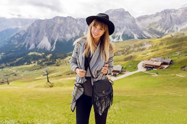 Donna giovane viaggiatore con cappello e zaino godendo di una splendida vista sulle montagne