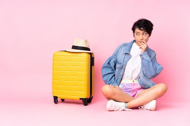 Donna giovane viaggiatore con la valigia che si siede sul pavimento sopra il muro rosa con dubbi e con espressione del viso confuso