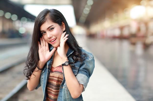 Donna giovane viaggiatore con treno in attesa di giacca jean