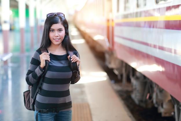 Donna giovane viaggiatore con zaino in attesa del treno