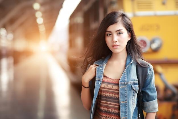 Donna giovane viaggiatore con zaino in attesa di un treno