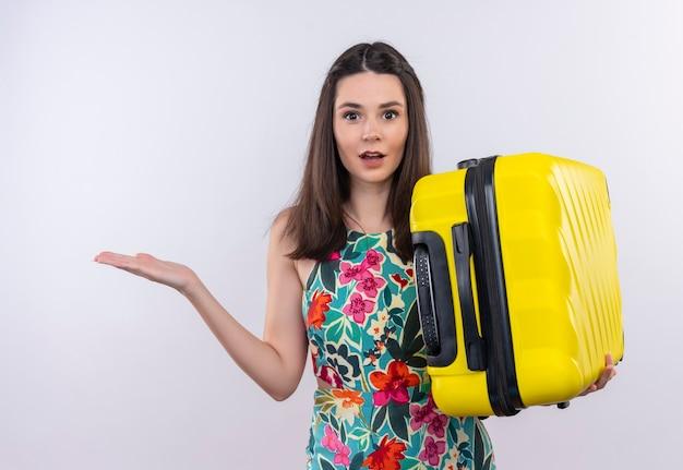 Donna giovane viaggiatore confuso che tiene la valigia sulla parete bianca isolata