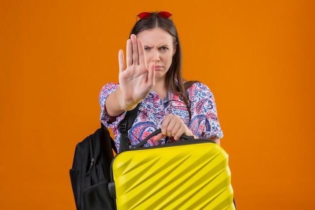Donna giovane viaggiatore scontento che indossa occhiali da sole rossi sulla testa in piedi con lo zaino che tiene la valigia con la mano aperta facendo il segnale di stop con gesto di difesa di espressione arrabbiata