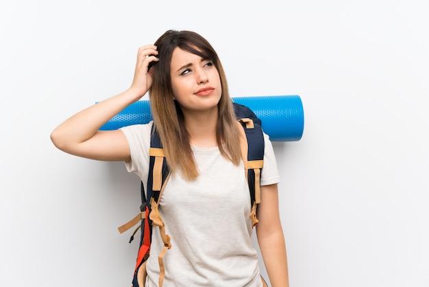Donna giovane viaggiatore su muro bianco con dubbi e con espressione del viso confuso