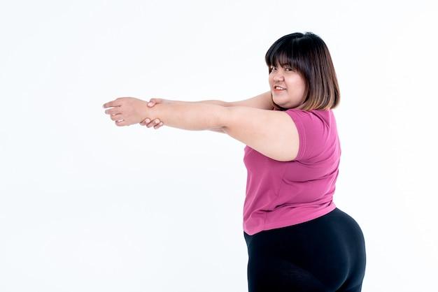 Donna grassa asiatica che allunga le braccia per rilassare i muscoli