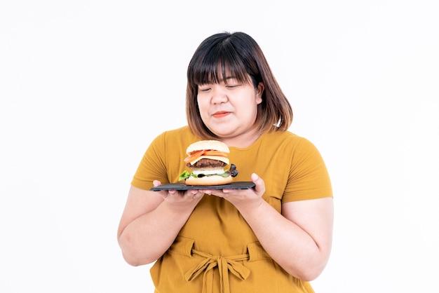 Donna grassa asiatica che sorride e che tiene hamburger