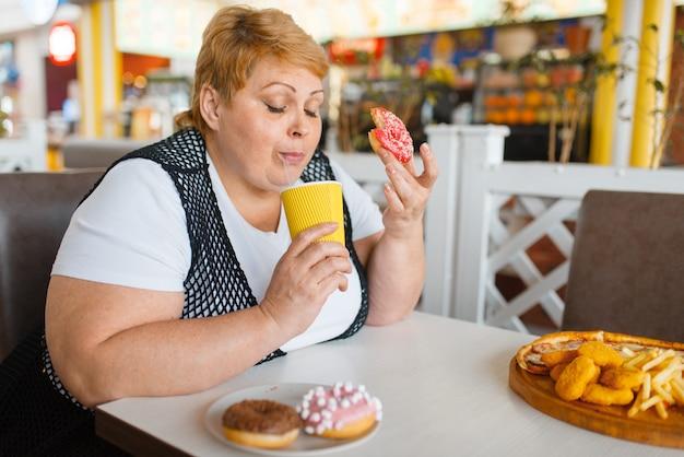 Donna grassa che mangia ciambelle in un ristorante fastfood